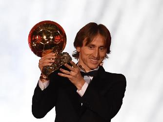 TOPSHOT - Real Madrid's Croatian midfielder Luka Modric brandishes the trophy after receiving the 2018 FIFA Men's Ballon d'Or award for best player of the year during the 2018 FIFA Ballon d'Or award ceremony at the Grand Palais in Paris on December 3, 2018. - The winner of the 2018 Ballon d'Or will be revealed at a glittering ceremony in Paris on December 3 evening, with Croatia's Luka Modric and a host of French World Cup winners all hoping to finally end the 10-year duopoly of Cristiano Ronaldo and Lionel Messi. (Photo by FRANCK FIFE / AFP)